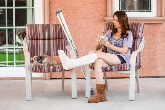 Pretty woman with broken leg in cast counts money while sitting outside on chair at home with her lazy dog  Royalty free stock photo