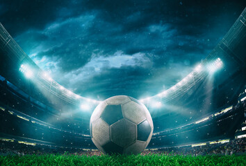 Close up of a soccer ball in the center of the stadium illuminated by the headlights