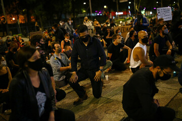 A man kneels as he participates in a demonstration in Mexico City against the death in Minneapolis police custody of George Floyd