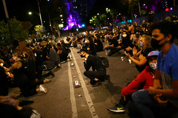 A woman kneels as she participates in a demonstration in Mexico City against the death in Minneapolis police custody of George Floyd