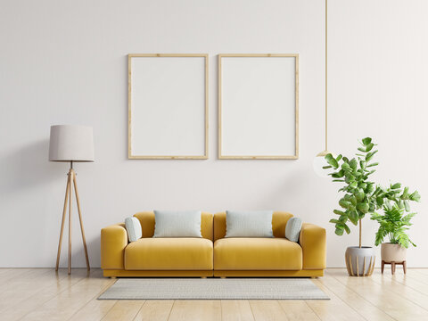 Poster mockup with vertical frame standing on floor in living room interior with yellow sofa.