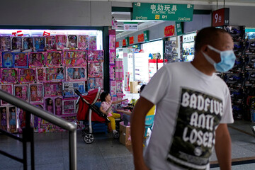 A man wearing face mask walks past a toy products stall at the Yiwu Wholesale Market following an outbreak of the novel coronavirus disease (COVID-19), in Yiwu