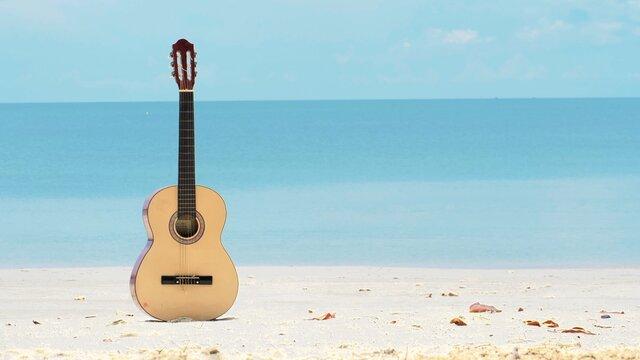 An acoustic guitar under summer sky on a beautiful sandy beach