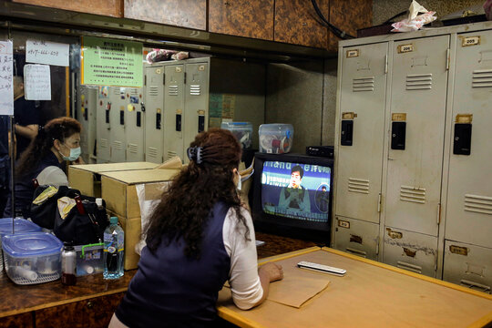 A staff watches a TV broadcast of daily updates on the coronavirus disease (COVID-19) from Taiwan's Centers for Disease Control and Prevention while waiting for customers at the break room of a massage parlour in Taipei