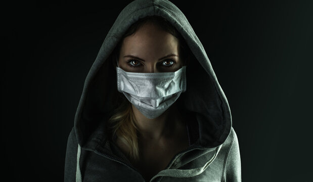 Dark photo of Young handsome man wearing medical protactive face mask in night street