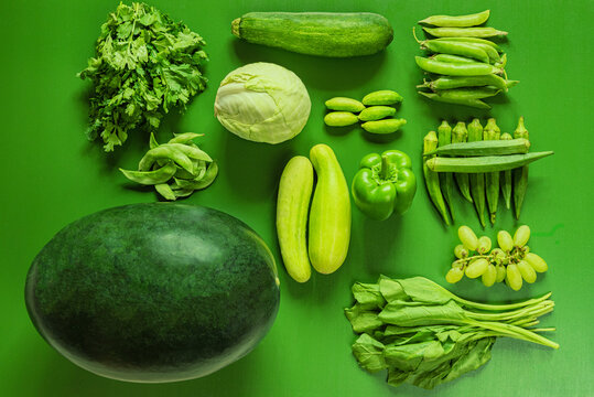 Assorted green vegetables and fruits on a green background