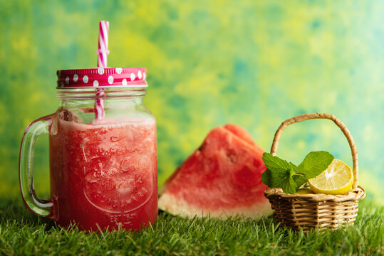Watermelon juice in a jar with watermelon pieces and lemon wedge and mint leaves in a basket