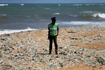 An environment protection unit police officer inspects while standing in a garbage area on a beach during an event to mark the World Environment Day in Colombo