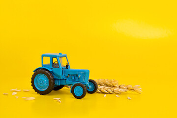 Toy blue retro tractor collects a crop of wheat on a yellow background. Copy space.