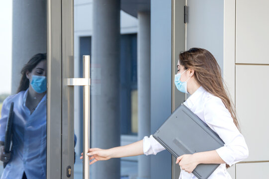 Young entrepreneur wearing a face mask outside during the Covid-19 coronavirus health crisis. Professional woman entering the office