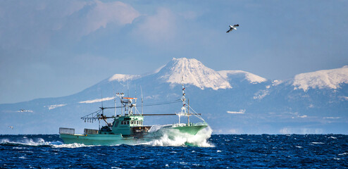 Photo sur Plexiglas Peche Fishing boat returns after fishing to its port. Against the backdrop of the island of Kunashir. Japan. The water area of Hokkaido. Kunashir Strait. Sea of Okhotsk.