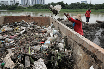 Workers clean up waste collected by a log boom by a river during World Environment Day, in Klang