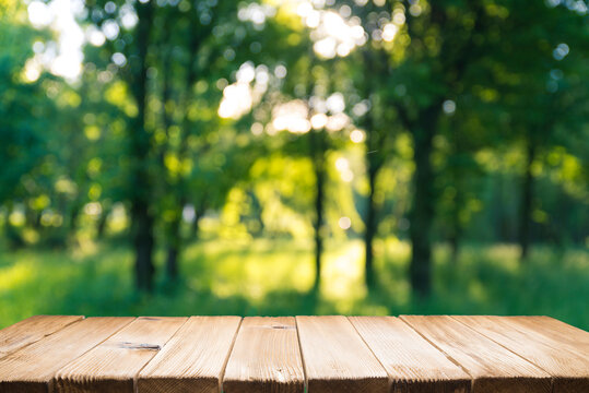 Empty wooden deck table with park bokeh background.