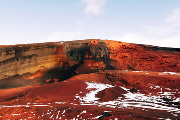 Poster Bordeaux Martian landscapes in Iceland. The red crater of The Seydisholar volcano. The quarry of red soil mining. White snow lies on red soil.