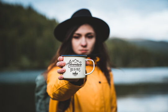 Beautiful girl with hat, backpack and yellow jacket holding outdoor mug or cup. Morning hot coffee in nature. The adventure begins outdoor concept. Travel and wanderlust