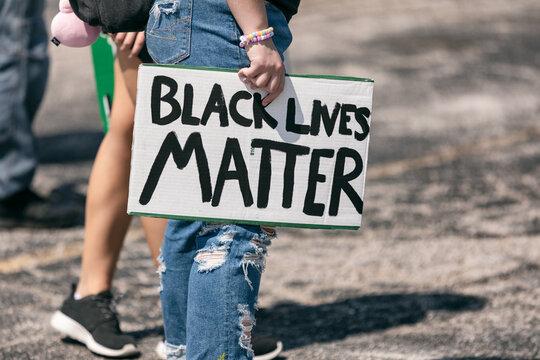 Midsection of man holding Black Lives Matter sign