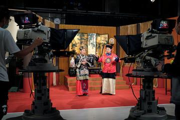 """Ng Chi-sam and Tsang Chi-ho, hosts of Radio Television Hong Kong (RTHK)'s satirical comedy show """"Headliner"""" react during a show rehearsal in Hong Kong"""