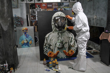 An artist wearing a protective suit paints a picture of a health worker as an appreciation for the service amid the coronavirus disease (COVID-19) outbreak, in Sleman