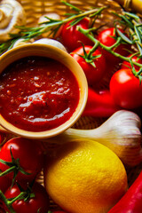 close up view of delicious tomato sauce with fresh ripe vegetables in basket
