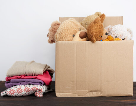 brown cardboard box filled with things and children's toys, concept of moving