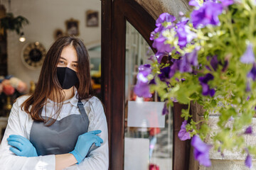 Coronavirus covid 19. Floral shop woman owner in gloves with face mask, open door after lockdown quarantine. Announcement we are open nv doors, flower shops, cafes, local, small businesses concept.