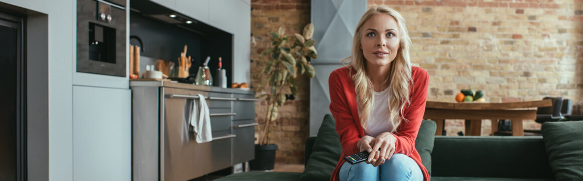 horizontal image of attentive young woman watching tv while sitting on sofa at home