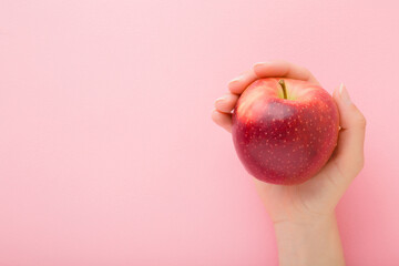 Young woman hand holding red apple on light pink table background. Fresh fruit. Pastel color. Closeup. Point of view shot. Empty place for text. Top down view Papier Peint