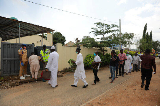 A security man checks people's temperature outside a mosque, as places of worship reopen after the relaxation of restrictions imposed to curb the spread of the coronavirus disease (COVID-19) in Abuja