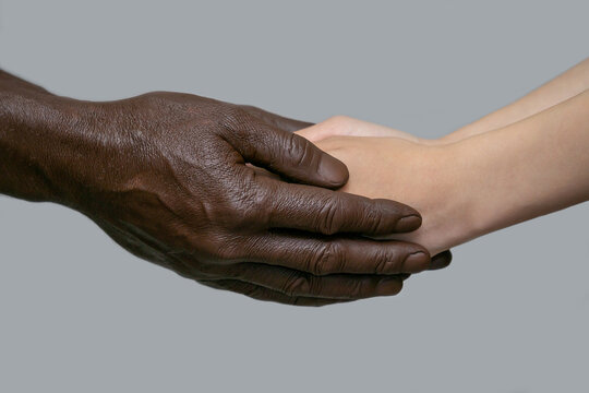 Black male hands hold white female human hands in their palms. The concept of inter-racial friendship, love, respect, and the fight against racism. Copy of the space, gray isolated background.