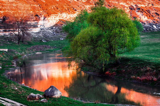 Beautiful landscape of summer hills with river in Moldova, Old Orhei. Zigzag river flows between valleys with willow trees and rocks at sunset. Travel background, Europe