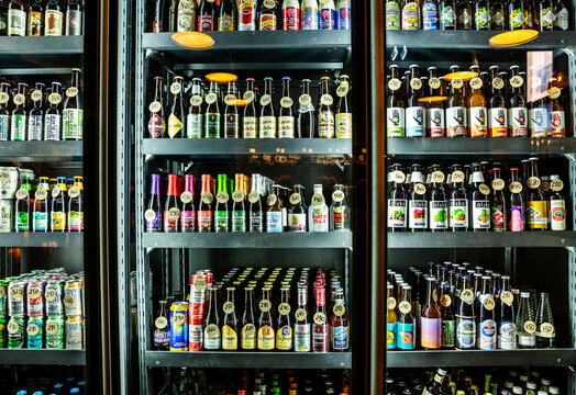 Moscow, Russia - May 18, 2019: Large selection of beer in the fridge behind the glass in the beer bar