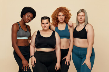 Diversity. Group Of Models With Different Figure Size And Body Types Portrait. International Friends In Sportswear Posing On Beige Background. Body Positive As Lifestyle.