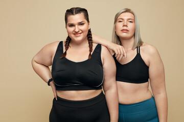 Workout. Plus Size Models Portrait. Confident Fitness Women In Sportswear Posing Against Beige Background. Body Positive As Lifestyle.