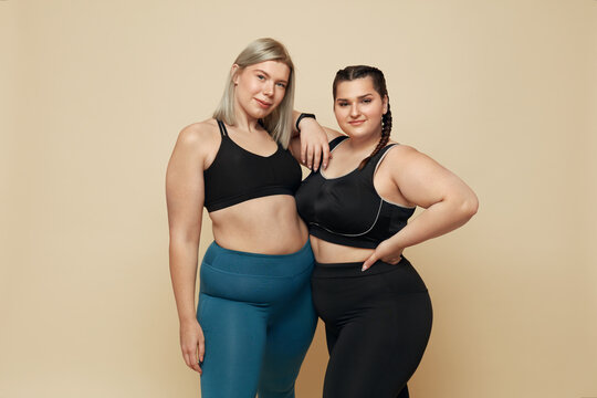 Body Positive. Plus Size Models Portrait. Confident Full-Figured Women In Sport Clothes Against Beige Background. Fitness For Active Lifestyle.