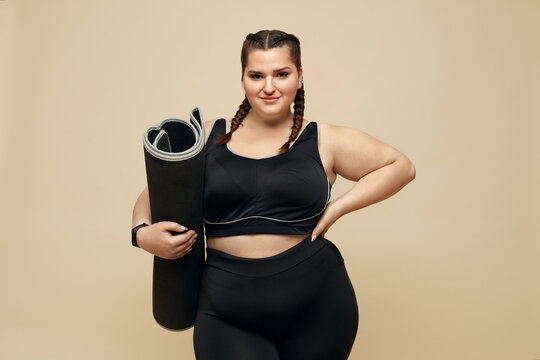 Fitness. Plus Size Model In Black Sportswear Portrait. Full-Figured Woman Holding Pilates Mat. Body Positive And Sport As Lifestyle.