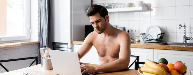sexy shirtless freelancer working on laptop on kitchen with fruits and coffee, website header