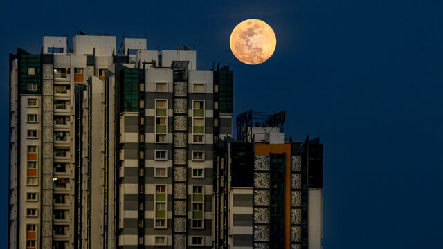 Strawberry Moon rising behind a building