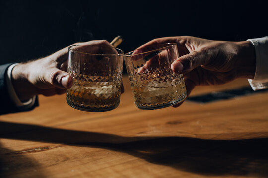 Close up of two men toasting with whiskey.