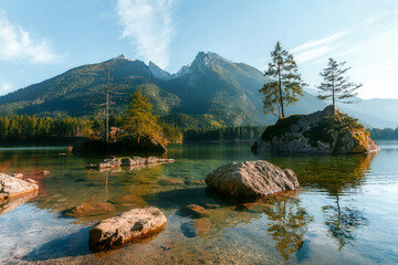Fotomurales - Awesome Sunny nature Scenery. Impressively beautiful Hintersee lake at sunrise. Scenic image of fairy-tale Landscape in sunlit, with Majestic Rocky Mountains and perfect sky on background. Bavarya