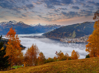 Fotomurales - Incredible Nature Landscape. Foggy morning during sunrise at Alpine lake in autumn. Colorful Sky over the Zeller Lake in Zell am See, Salzburger Land, Austria. Creative image. Natural Background