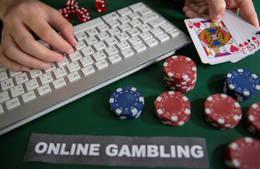 "Person holds cards near keyboard, chips, dice and ""Online Gambling"" words in this illustration picture"
