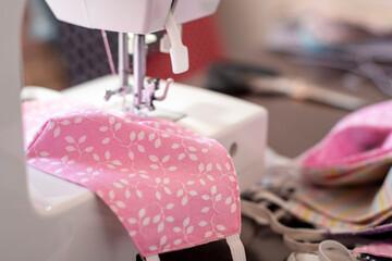 Selective focus on handmade cotton fabric cotton face mask in sewing process. Protection against saliva, coronavirus, cough, dust, pollution, virus, bacteria, COVID-19, coronavirus.