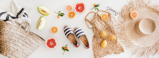 Summer mood layout. Flat-lay of summer natural espadrillas, straw sunhat, beach rafia and net bag, beach towel, sunglasses and fresh fruit over white plain background, top view