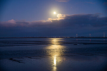 Low tide in Delfzijl during full moon with the view on wind electricity with Germany on the opposite shore on Ems river