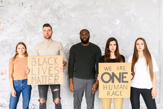 """A protest against cruelty and racism. Multi-racial group of young people with signs """"black lives matter"""", """"we are one human race"""" in studio"""