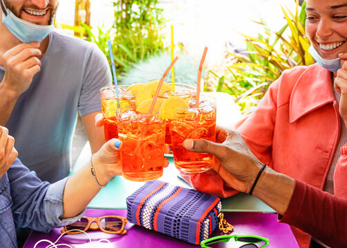 Friends drinking coktail in a restaurant bar outside in summer days with face mask on to be protected from coronavirus - Happy people cheering with spritz and having fun