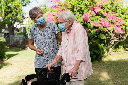 Two older ladies wearing masks in garden
