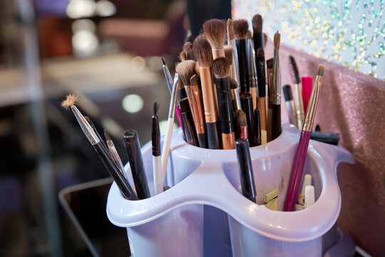 Professional visagiste brushes aisle in makeup studio. Set of a cosmetic brushes . Professional visage brushes for face makeup on table.Body art paint in beauty salon.Close up brush kit .