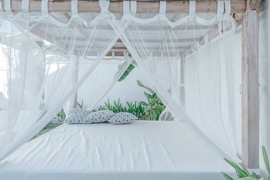 Gazebo with a wooden bed under a mosquito grid on a outside