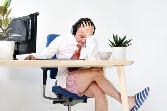 The male manager works remotely at home, holds online meetings. He is experiencing is tired and embarrassed. He is wearing a shirt and tie, underpants and slippers. Stay home and quarantine.